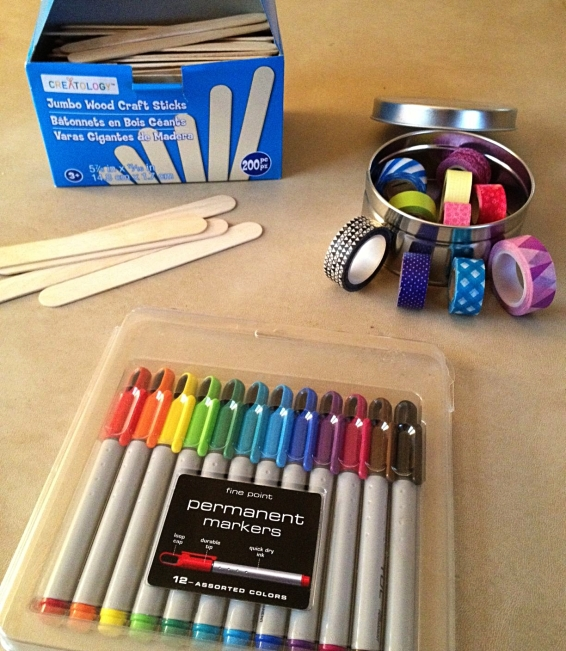 Got my supplies: my trusty set of permanent markers, a massive box of Jumbo popsicle sticks, and plenty of funky washi tape (the Whimeybox tapes are the two larger rolls outside of the tin, black and white tiny triangles on the far left and pink/purple/translucent large triangles on the far right)